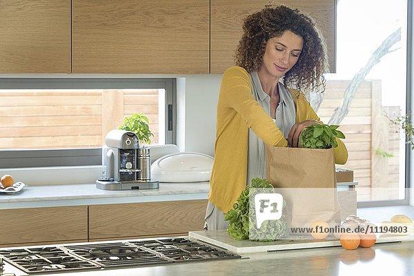 Frau  die Essen aus einer Papiertüte in der Küche holt.