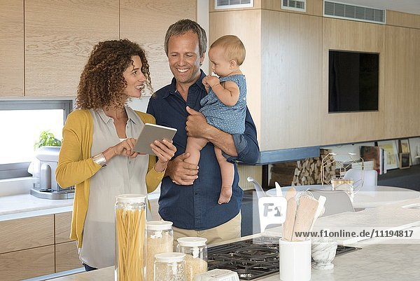 Couple using digital tablet with their daughter in the kitchen