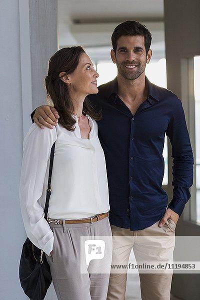 Glückliches Paar steht am Eingang eines Hauses