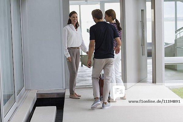 Fröhliche reife Frau begrüßt ihre Freunde am Eingang