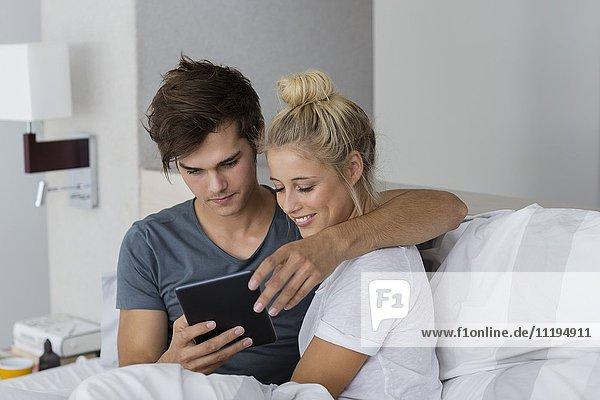 Paar mit einem digitalen Tablett auf dem Bett