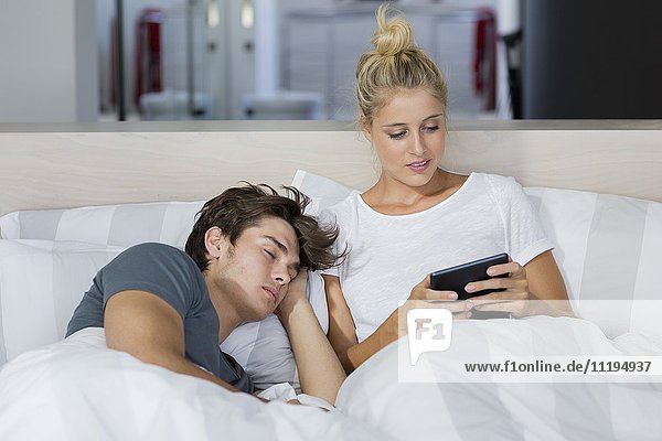 Junge Frau  die ein digitales Tablett benutzt  während ihr Freund in ihrer Nähe schläft.