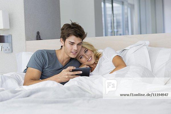 Ein Paar sieht sich einen Film auf einem digitalen Tablett auf dem Bett an.