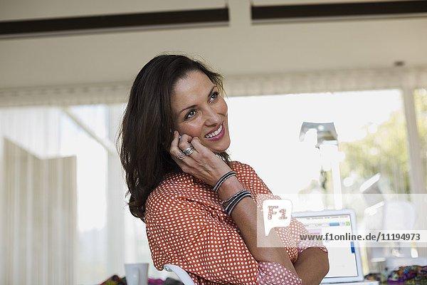 Glückliche Modedesignerin im Gespräch mit dem Handy