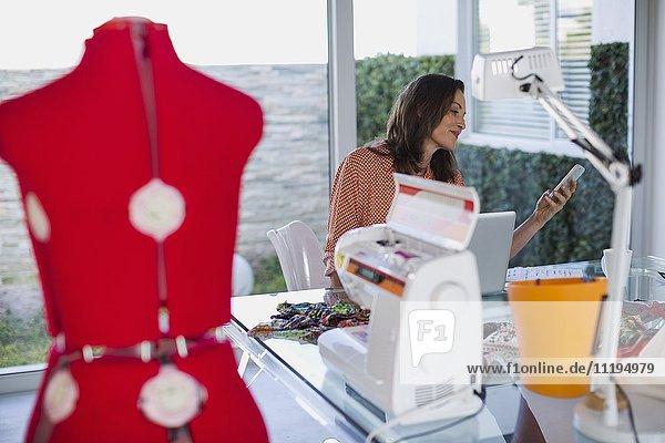 Kleidungsdesigner mit dem Handy