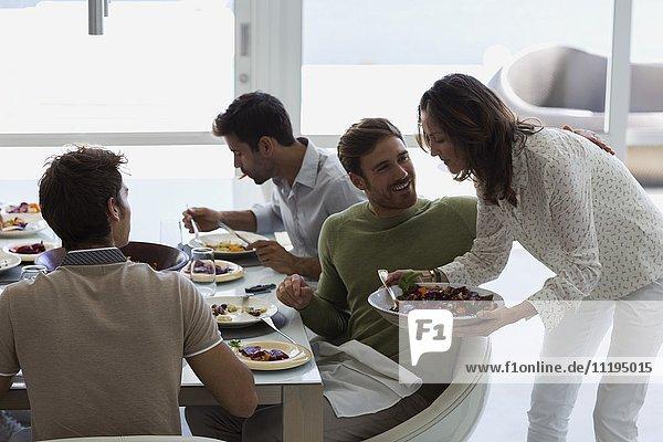 Frau serviert ihren Freunden Essen am Esstisch