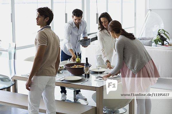 Freunde arrangieren Essen auf dem Tisch