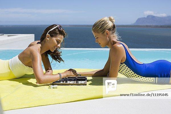 Glückliche Freundinnen beim Tic-Tac-Toe spielen am Pool