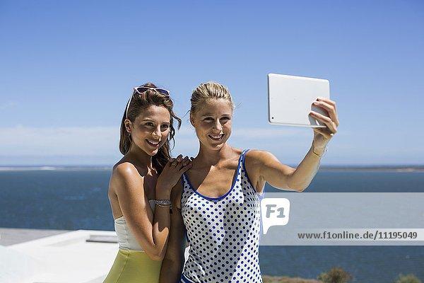 Weibliche Freunde  die Selfie für sich selbst mit einem digitalen Tablett nehmen