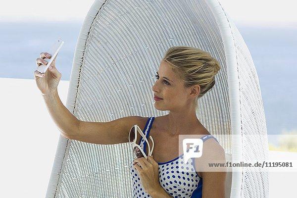 Schöne Frau sitzt in Korbschaukel und nimmt Selfie mit einem Smartphone.