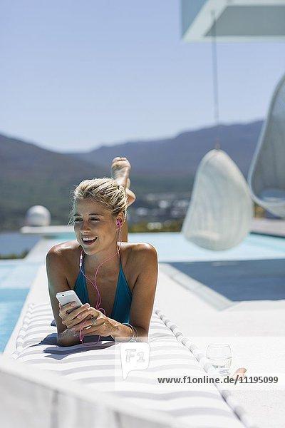 Junge Frau beim Musikhören mit Smartphone am Pool