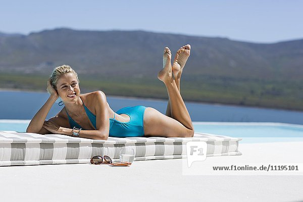 Schöne junge Frau entspannt sich am Pool
