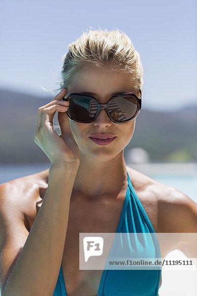 Nahaufnahme einer glücklichen jungen Frau mit Sonnenbrille