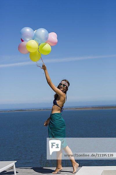 Glückliche junge Frau mit Luftballons