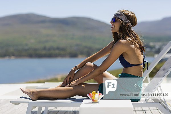 Young beautiful woman sitting on lounge chair
