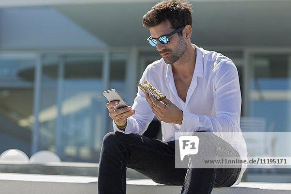 Mid Erwachsene Mann mit einem Smartphone und essen Sandwich