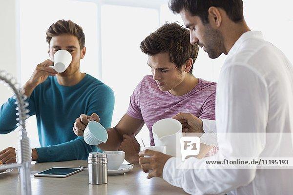 Drei männliche Freunde trinken Kaffee