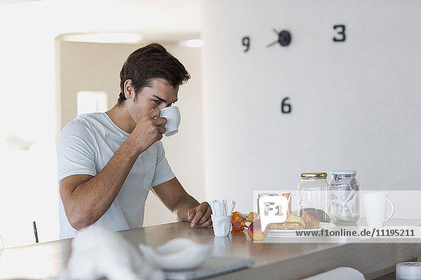 Nahaufnahme eines jungen Mannes beim Kaffeetrinken