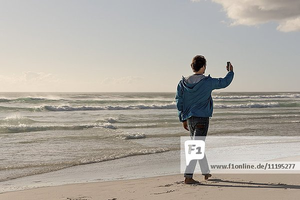 Happy young man using a phone on beach
