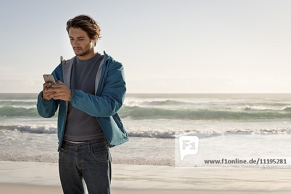Happy young man using a mobile phone on beach
