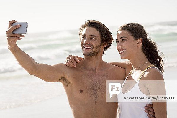 Young couple taking selfie of themselves with a smart phone