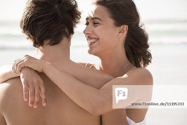 Glückliche junge Frau  die ihren Freund umarmt.