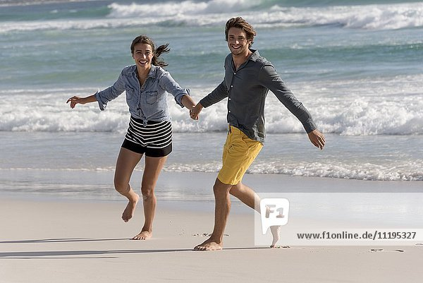Porträt eines glücklichen jungen Paares am Strand