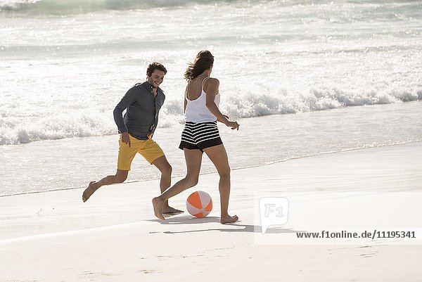 Glückliches junges Paar beim Spielen mit einem Strandball