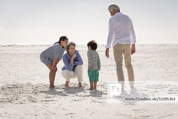 Zufriedene Großeltern mit Enkelkindern am Strand