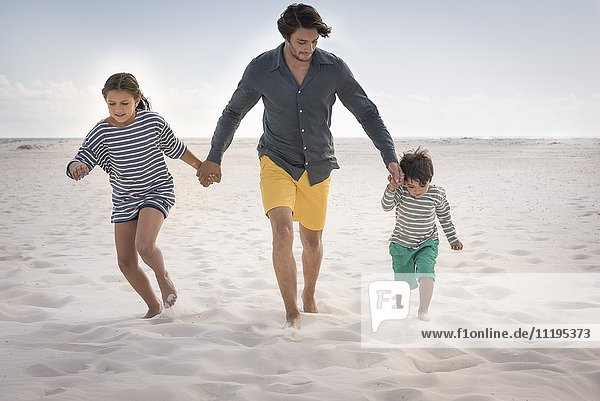 Happy father running with his children on beach