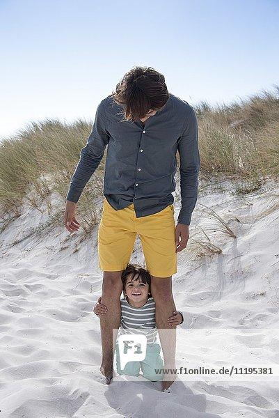 Glücklicher Vater und Sohn genießen am Strand