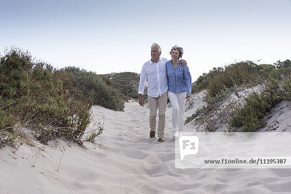 Happy senior couple walking on beach