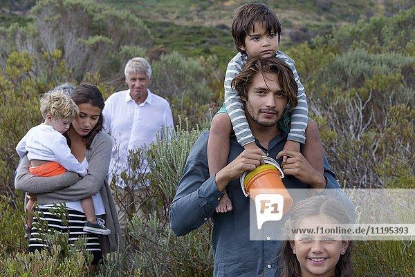 Glückliche Mehrgenerationen-Familie beim Wandern in der Landschaft