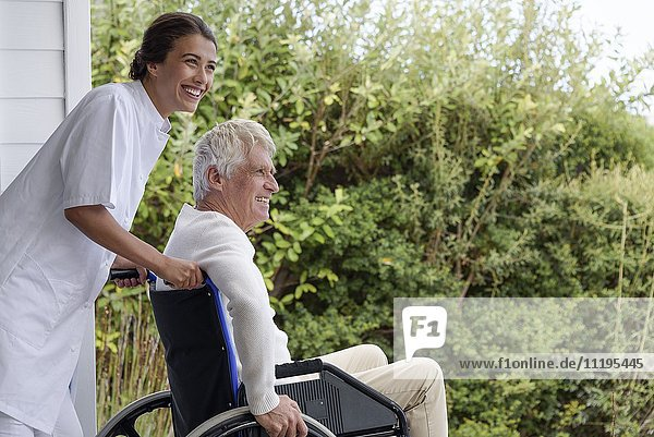 Krankenschwester als Assistentin eines älteren Mannes im Rollstuhl auf der Veranda