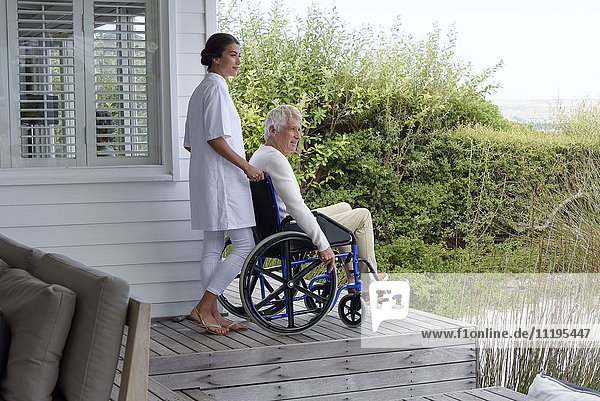 Female nurse assisting senior man in wheelchair on porch