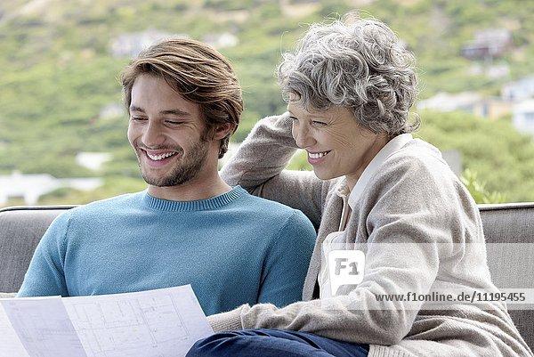 Glückliche Mutter mit ihrem erwachsenen Sohn beim Lesen einer Blaupause im Freien.