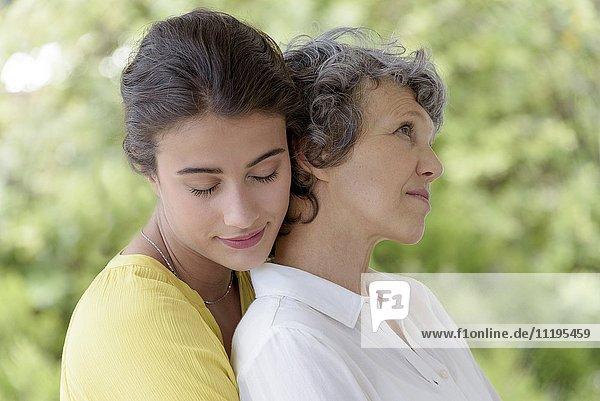 Liebevolle junge Frau  die ihre Mutter umarmt.