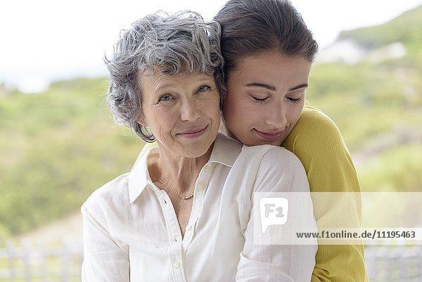 Liebevolle junge Frau  die ihre Mutter im Freien umarmt.