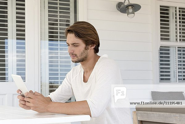 Junger Mann mit einem digitalen Tablett zu Hause