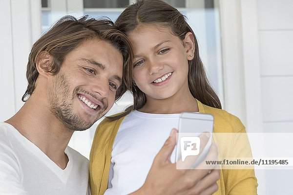 Happy father with his little daughter taking a selfie with camera phone at home