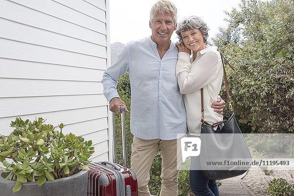 Glückliches Seniorenpaar steht mit Koffer vor dem Haus