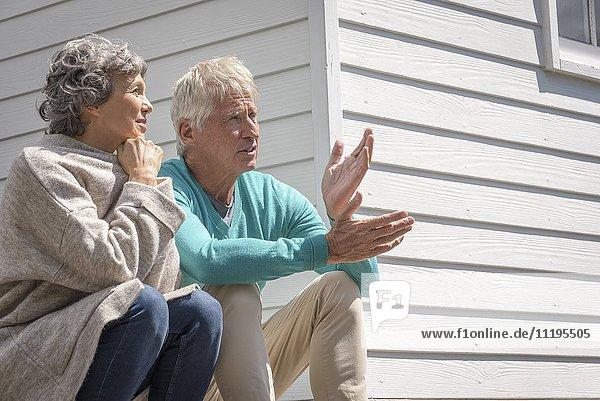 Seniorenpaar im Gespräch vor dem Haus