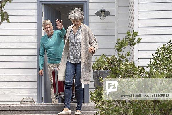 Fröhlicher älterer Mann winkt seiner Frau mit Koffer auf der Treppe zu.