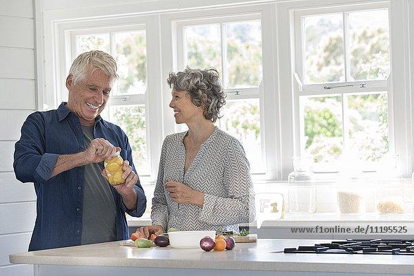 Fröhliches Seniorenpaar bei der Zubereitung des Essens in der Küche