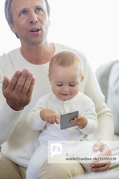 Glücklicher Vater und seine kleine Tochter beim Spielen mit dem Handy auf der Couch