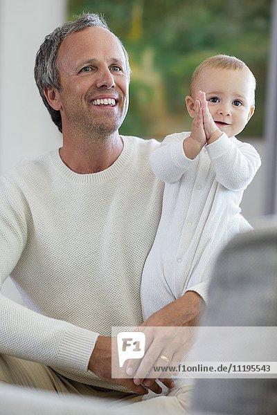 Glücklicher Vater mit seiner süßen kleinen Tochter im Wohnzimmer