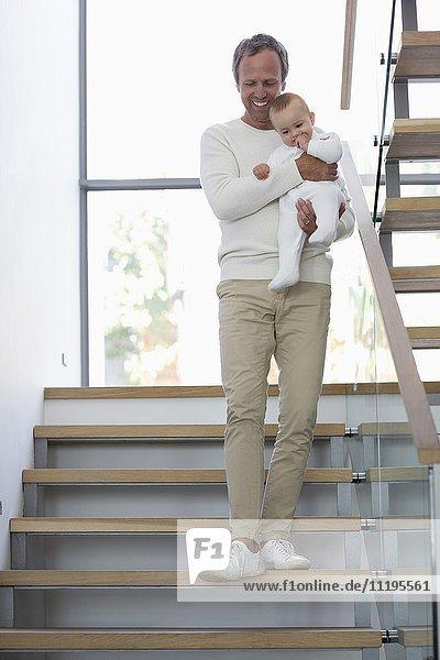Glücklicher Vater mit seiner süßen kleinen Tochter auf der Treppe.