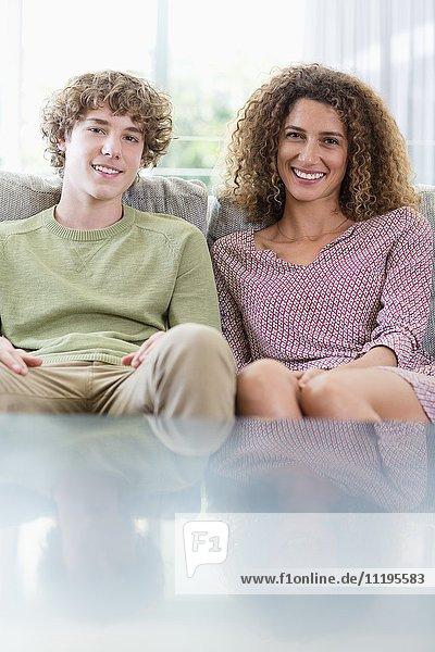 Porträt einer glücklichen Mutter und eines glücklichen Sohnes auf der Couch im Wohnzimmer