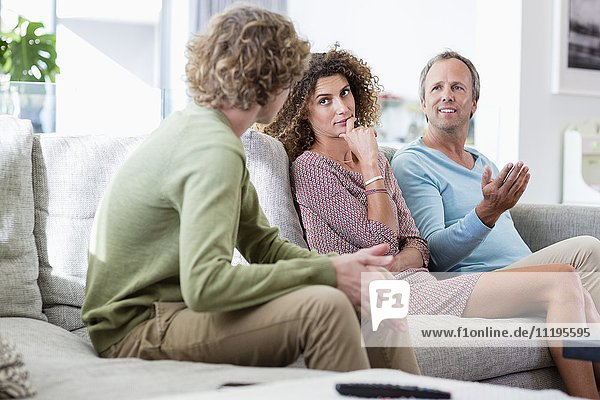 Happy family talking in a living room at home
