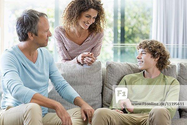 Glückliche Familie lächelt in einem Wohnzimmer zu Hause